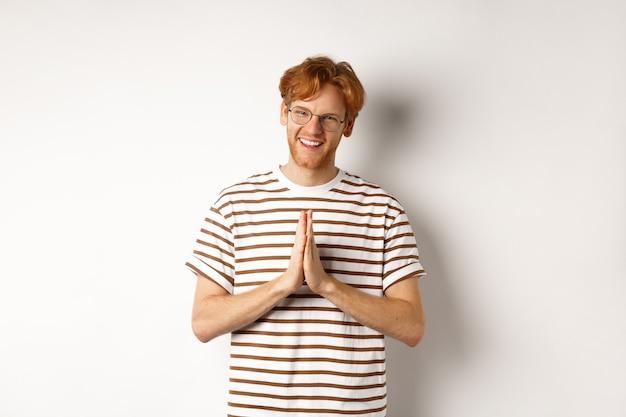 Jovem bonito de óculos, cabelo ruivo, mostrando o gesto namastê e sorrindo, agradecendo, grato em pé sobre fundo branco.