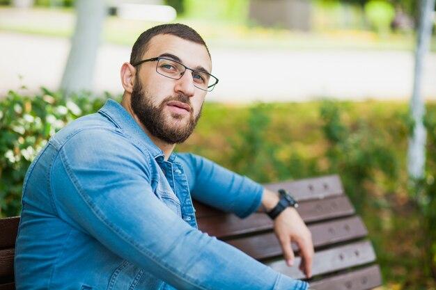 Jovem bonito de óculos com barba relaxar ao ar livre. closeup retrato masculino de um cara com jaqueta jeans, estilo jeans, aparência hipster