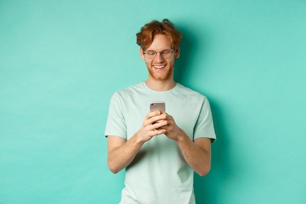 Jovem bonito de óculos com cabelo ruivo bagunçado lendo mensagem no celular, sorrindo e olhando para a tela, em pé sobre o fundo da casa da moeda.
