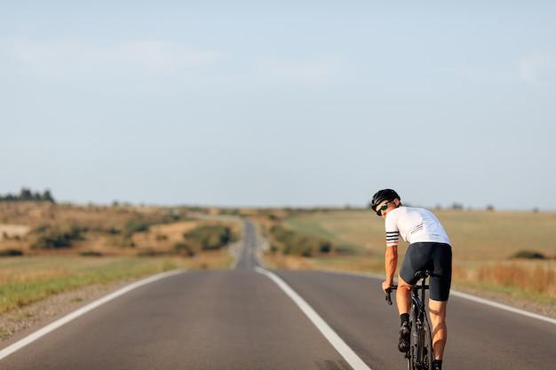 Jovem bonito de óculos e capacete andando de bicicleta no meio de uma estrada de asfalto