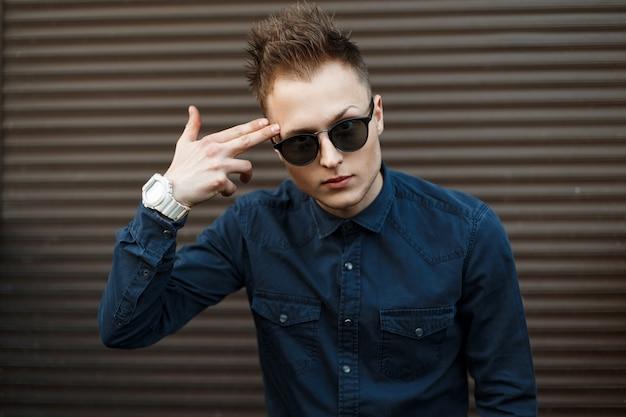 Jovem bonito de óculos escuros e camisa azul mostra uma pistola com os dedos perto da parede de metal