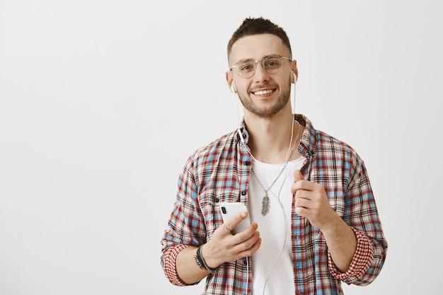 Jovem bonito de óculos, posando com seu telefone e fones de ouvido