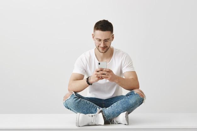 Jovem bonito de óculos posando com seu telefone