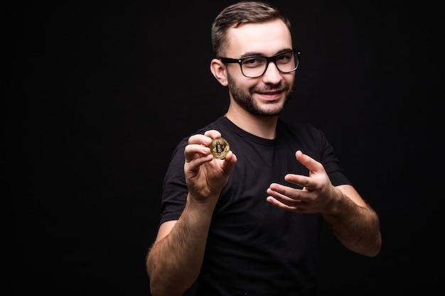 Jovem bonito de óculos usa camisa preta e apresenta bitcoin isolado no preto
