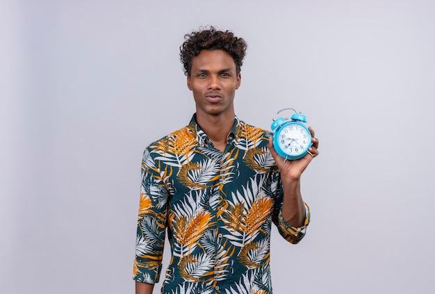 Jovem bonito de pele escura com cabelo encaracolado, camisa estampada de folhas, segurando um despertador azul e mostrando as horas em um fundo branco