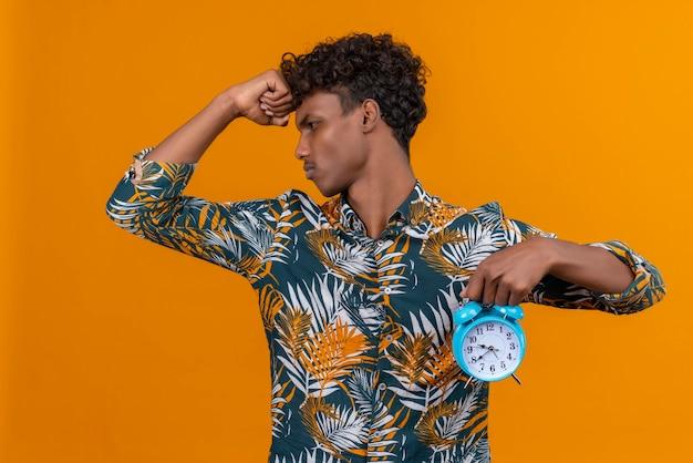 Jovem bonito de pele escura estressado com cabelo encaracolado em uma camisa estampada de folhas segurando um despertador azul e mostrando as horas em um fundo laranja