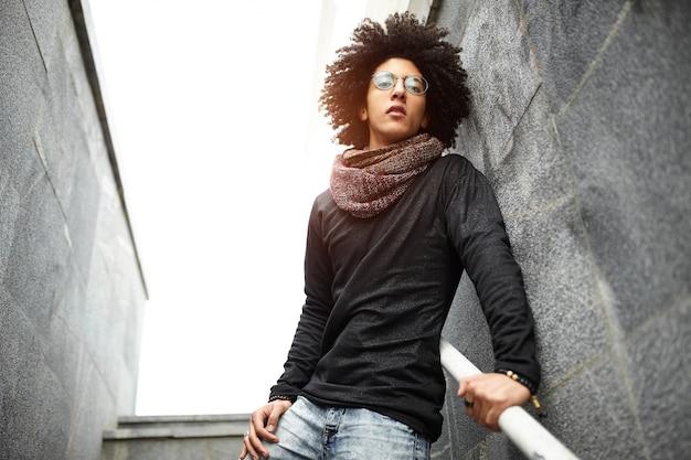 Jovem bonito de raça mista com um corte de cabelo em roupas da moda
