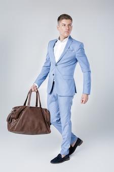 Jovem bonito de terno azul segurando uma bolsa de couro