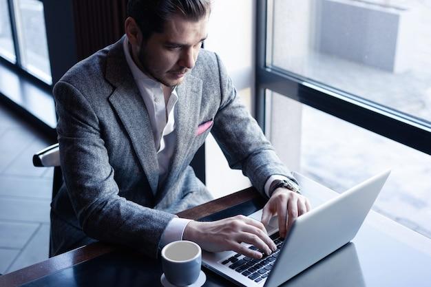 Jovem bonito de terno completo usando o computador enquanto está sentado no café