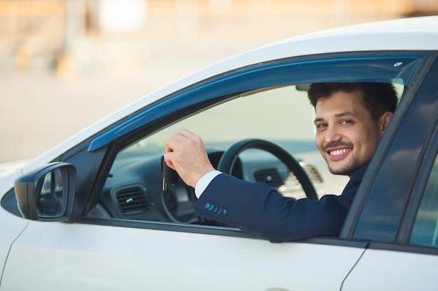 Jovem bonito de terno sentado em um carro no verão com a chave do carro