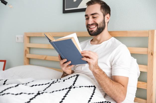 Jovem bonito deitado na cama, trabalhando em um laptop, lendo um livro