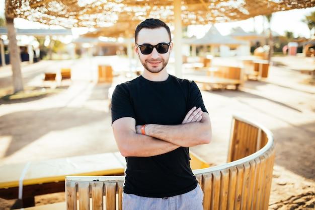 Jovem bonito descansando em restaurante de praia à beira-mar
