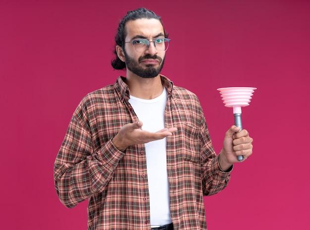 Jovem, bonito, descontente, cara de limpeza vestindo uma camiseta segurando e apontando para o êmbolo isolado na parede rosa