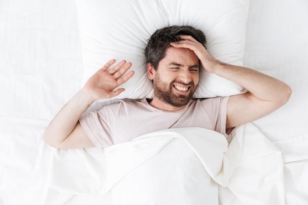 Jovem bonito descontente com dor de cabeça pela manhã, debaixo do cobertor na cama