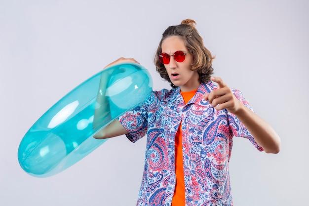 Jovem bonito descontente usando óculos escuros vermelhos segurando um anel inflável apontando para a câmera com expressão de raiva em pé