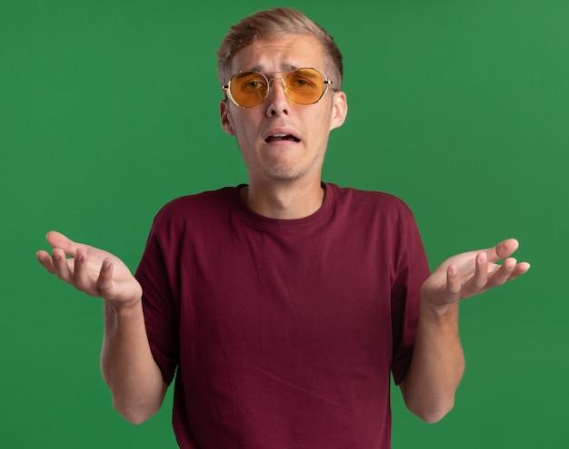 Jovem bonito descontente, vestindo camisa vermelha e óculos, espalhando as mãos isoladas na parede verde
