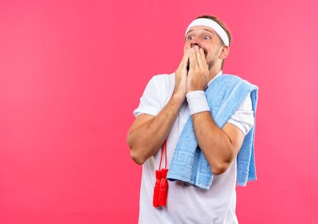 Jovem bonito desportivo assustado usando bandana e pulseiras, colocando as mãos na boca, olhando para o lado, com corda de pular e toalha nos ombros isolados no espaço rosa