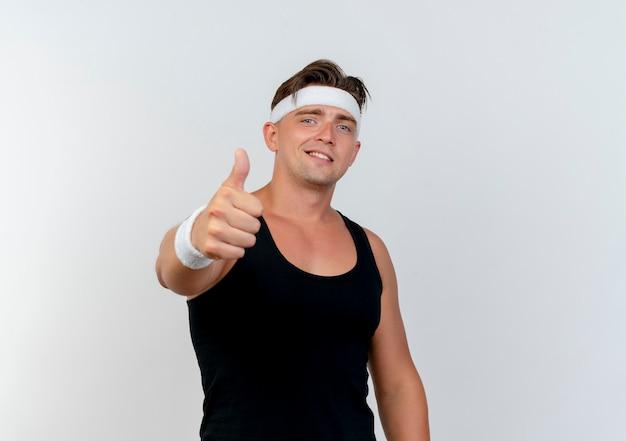 Jovem, bonito, desportivo, sorridente, usando fita para a cabeça e pulseiras mostrando o polegar na frente, isolado na parede branca