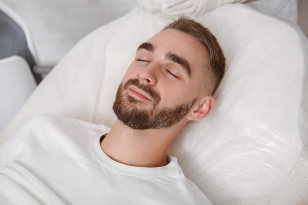 Jovem bonito dormindo em sua cama de hospital após a cirurgia
