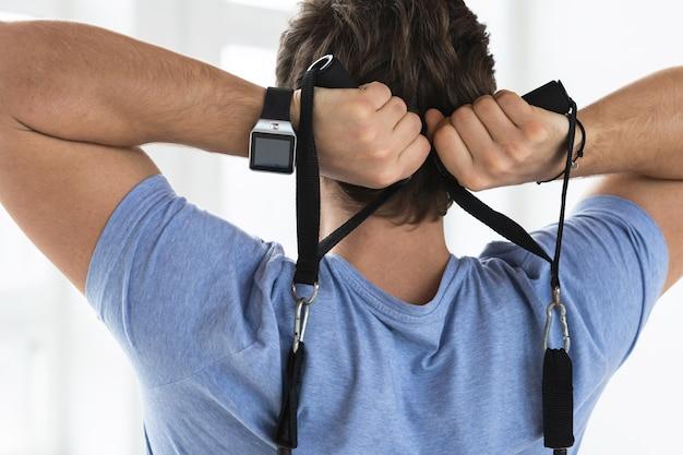 Jovem bonito durante o treino com elásticos de resistência no ginásio. exercício de extensão aérea de tríceps.