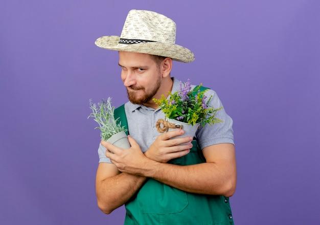 Jovem bonito e astuto jardineiro eslavo de uniforme e chapéu segurando vasos de flores com as mãos cruzadas e mordendo o lábio isolado na parede roxa com espaço de cópia
