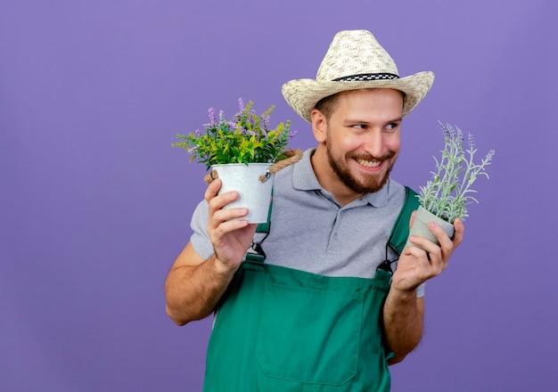 Jovem bonito e astuto jardineiro eslavo de uniforme e chapéu segurando vasos de flores, olhando para o lado e sorrindo, isolado na parede roxa com espaço de cópia