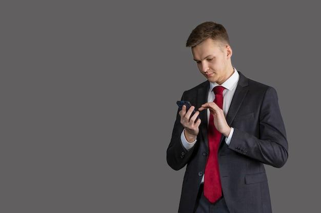 Jovem bonito e atraente de terno usando telefone, comunicando-se no smartphone, lendo notícias, mensagem. conceito de negócios.