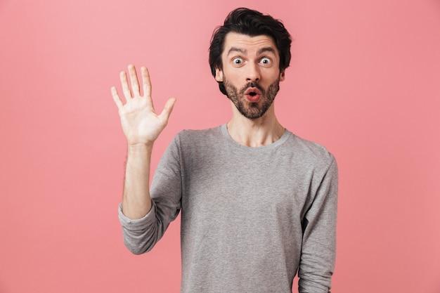 Jovem bonito e barbudo homem moreno usando um suéter em pé rosa, acenando com a mão