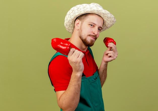 Jovem bonito e bonito jardineiro eslavo de uniforme e chapéu em pé na vista de perfil segurando pimentas e parecendo isolado