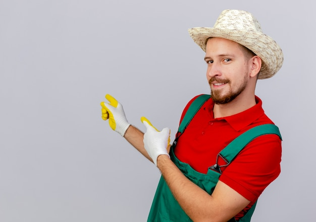 Jovem bonito e bonito jardineiro eslavo de uniforme, usando luvas de jardinagem e chapéu, em vista de perfil, apontando para o lado isolado