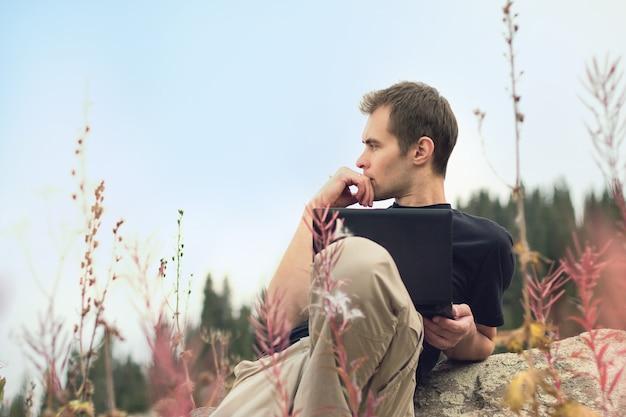 Jovem bonito e concentrado freelancer trabalhando em um laptop ao ar livre nas montanhas. freelance
