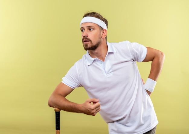 Jovem bonito e confiante homem desportivo usando bandana e pulseiras, colocando o braço no taco de beisebol e a mão na cintura, olhando para o lado isolado na parede verde com espaço de cópia