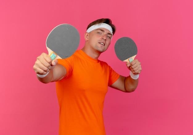 Jovem bonito e confiante homem desportivo usando bandana e pulseiras, segurando e esticando raquetes de pingue-pongue isoladas em rosa com espaço de cópia