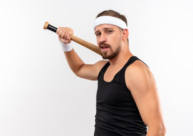 Jovem bonito e confiante homem esportivo usando bandana e pulseiras segurando um taco de beisebol isolado na parede branca