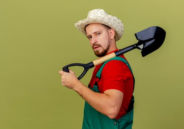 Jovem bonito e confiante jardineiro eslavo de uniforme e chapéu de pé em vista de perfil, segurando a pá no ombro e parecendo isolado