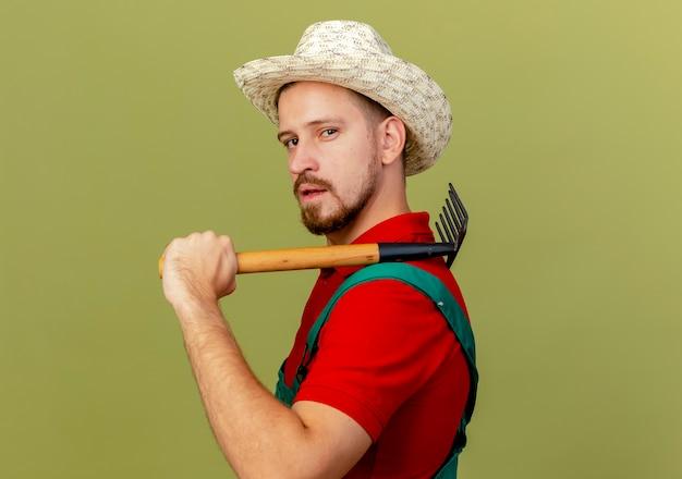 Jovem bonito e confiante jardineiro eslavo de uniforme e chapéu em pé na vista de perfil, segurando o ancinho no ombro, parecendo isolado