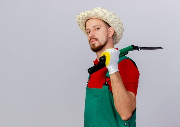 Jovem bonito e confiante jardineiro eslavo de uniforme e chapéu em vista de perfil, segurando podadores isolados no ombro