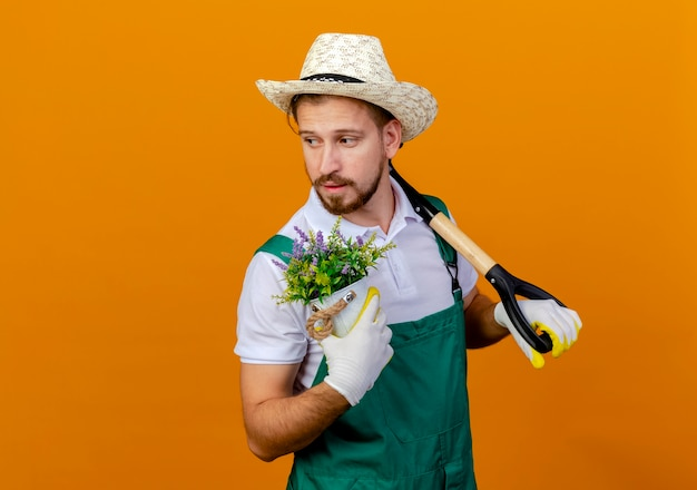 Jovem bonito e confiante jardineiro eslavo de uniforme, usando chapéu e luvas de jardinagem, segurando a pá no ombro e segurando o vaso de flores olhando para o lado isolado