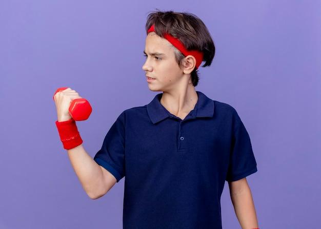 Jovem bonito e confiante rapaz desportivo usando bandana e pulseiras com aparelho dentário segurando e olhando para um halter isolado na parede roxa
