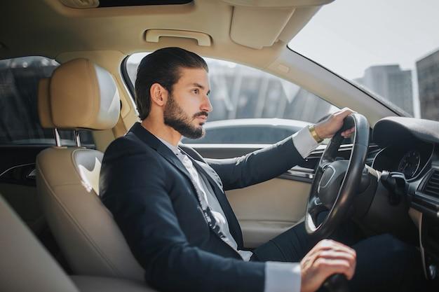 Jovem bonito e confiante senta-se no carro e olha para a frente. ele dirige carro. parece luxo por dentro. ele segura uma mão no volante e outra no freio de mão.