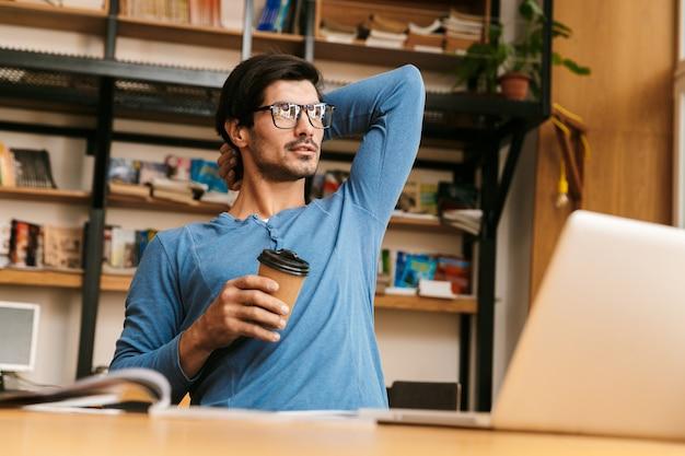 Jovem bonito e confiante sentado na mesa da biblioteca, trabalhando / estudando, usando um laptop, segurando uma xícara de café para viagem