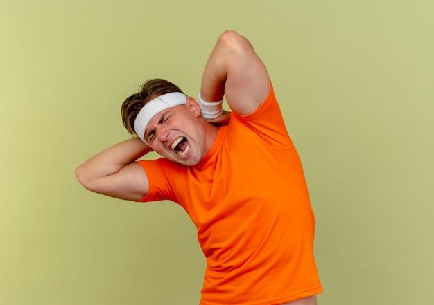 Jovem bonito e desportivo dolorido usando bandana e pulseiras, colocando as mãos atrás do pescoço, isolado em verde oliva com espaço de cópia