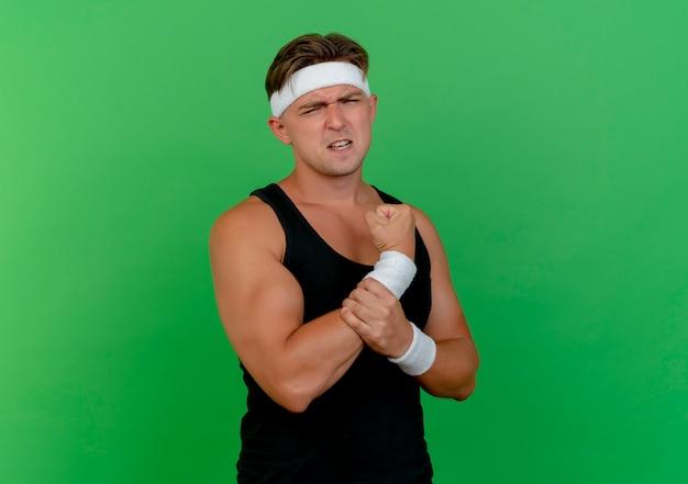 Jovem bonito e desportivo dolorido usando bandana e pulseiras segurando seu pulso isolado em verde com espaço de cópia