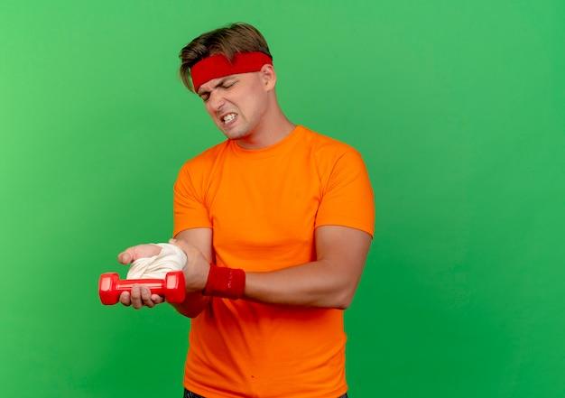 Jovem bonito e desportivo dolorido usando bandana e pulseiras, segurando um haltere e o pulso ferido envolto em uma bandagem isolada em verde com espaço de cópia