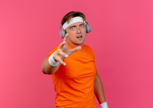 Jovem bonito e desportivo impressionado usando bandana, pulseiras e fones de ouvido estendendo a mão isolada em rosa