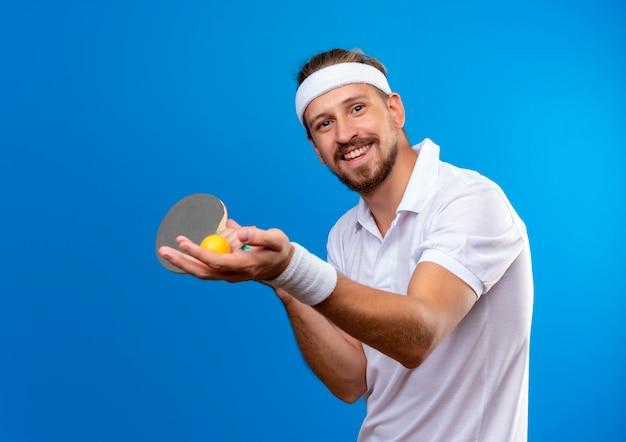 Jovem, bonito e desportivo sorridente, usando bandana e pulseiras segurando raquetes de pingue-pongue com uma bola isolada no espaço azul