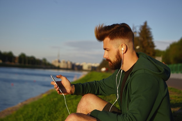 Jovem bonito e elegante com penteado estiloso e barba espessa curtindo uma manhã tranquila de verão ao ar livre, sentado à beira do lago e ouvindo músicas usando o aplicativo online em seu telefone celular