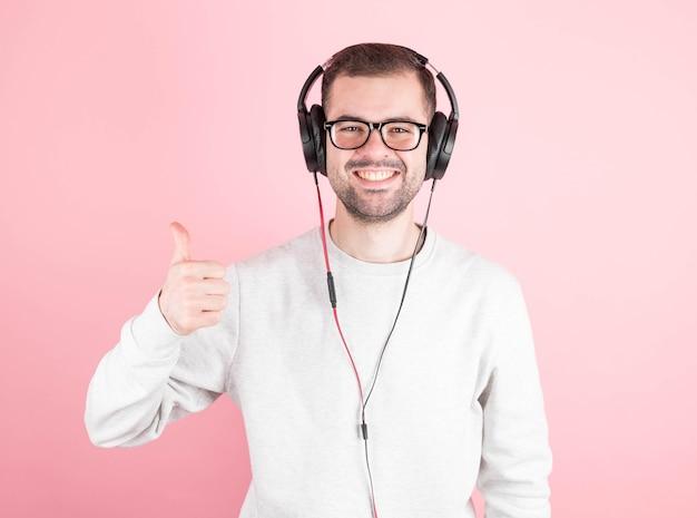 Jovem bonito e elegante em fones de ouvido, ouvindo boa música, mostrando um super sinal, pisando rosa