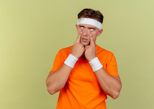 Jovem bonito e esportivo entediado usando bandana e pulseiras puxando para baixo as pálpebras isoladas em verde oliva com espaço de cópia