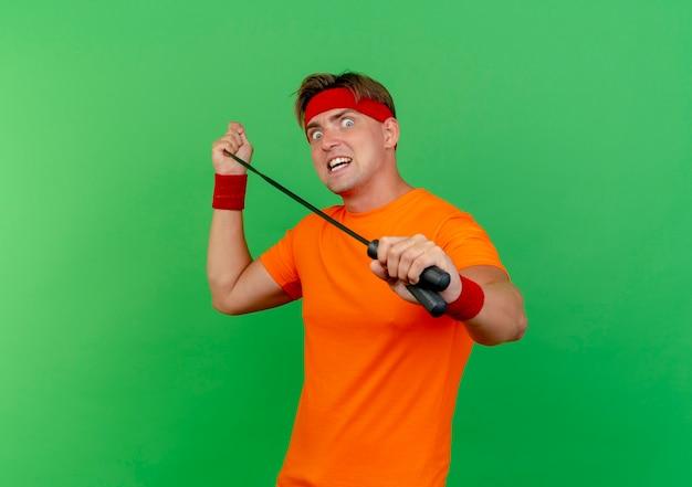 Jovem bonito e esportivo impressionado usando bandana e pulseiras puxando corda de pular isolada no verde